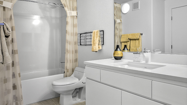 Evolve Apartments - Bathroom with White Furnishings, Toilet, Shower, and Mirror.