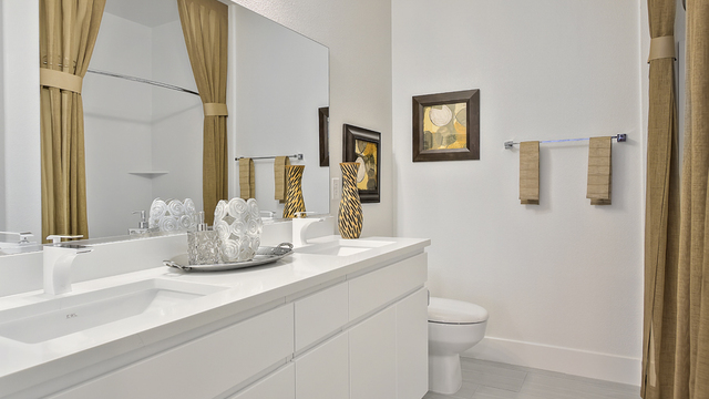 EVOLVE Apartments - Apartment Bathroom with White & Gold Furnishing, Toilet, and Sink.