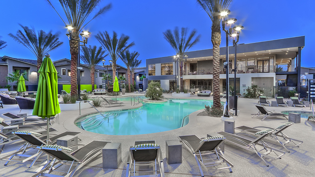 Evolve Apartments - Community Pool Area at Night with Palm Trees, Lounge Chairs, and Apartments in View