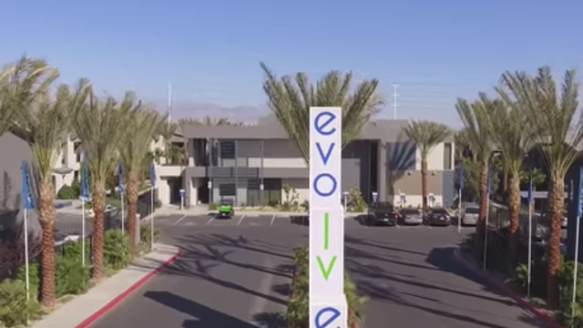 Evolve Apartments - Entranceway with Sign, Palm Trees, and Front Office